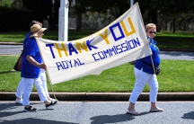Members of the Care Leavers Australasia Network hold up a banner thanking an Australian government commission on preventing child sexual abuse as they await a final report outside Government House in Canberra, Australia on December 15, 2017.