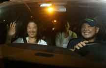three people inside car, man driving, woman in passenger seat smiling and waving, one more person in back