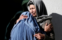 Afghan women mourn inside a hospital compound after a suicide attack in Kabul,