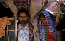 Rohingya refugees Saddam Hussein, 23, and his wife Shofika Begum, 18, pose in their temporary shelter at the Kutupalong refugee camp near Cox's Bazar, Bangladesh