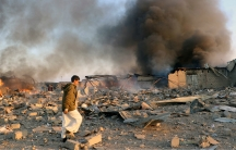 Smoke rises as people inspect damage at the site of airstrikes in the city of Saada, Yemen, Jan. 6, 2018.