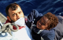 Man on a boat lifting a young child to hand to rescuers