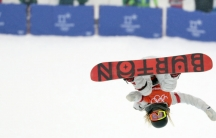 Woman on snowboard, in air, upside down in front of onlookers