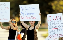 Angelina Lazo (C), an 18-year-old senior at Marjory Stoneman Douglas High School, lost two friends in the shooting at her school. She joined other gun control proponents with placards at a street corner in Coral Springs, Florida, on Feb. 16, 2018.