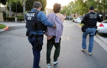 "A man with ""POLICE ICE"" protective vest leads a man in handcuffs down street, with another officer with ""POLICE FEDERAL AGENT"" on vest on the right"