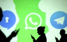 Silhouettes of mobile users are seen next to logos of social media apps Signal, Whatsapp and Telegram projected on a screen in this picture illustration taken March 28, 2018.