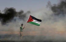 A demonstrator holds a Palestinian flag during clashes with Israeli troops at a protest where Palestinians demand the right to return to their homeland, near the Israel-Gaza border in the southern Gaza Strip on April 13, 2018.