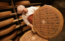 A Swiss cheesemaker inspects a large wheel of cave-aged Gruyere cheese. Such cheeses can be windows into the culture and geography of the places where they're made.