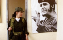 "A Colombian female leftist rebel looks at the photo of legendary guerrilla leader Ernesto ""Che"" Guevara in a temporary rebel headquarters in San Vicente del Caguan in 1999."