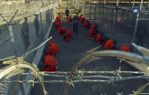 Detainees in orange jumpsuits sit in a holding area under the watchful eyes of military police during in-processing to the temporary detention facility at Naval Base Guantanamo Bay in January 2002.