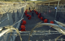 Detainees in orange jumpsuits sit in a holding area under the watchful eyes of military police during inprocessing at the temporary detention facility at Guantanamo Bay's Camp X-Ray in this January 11, 2002 file photograph.
