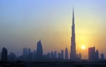 The Burj Khalifa (C) skyscraper is seen as the sun sets over Dubai on Oct. 5, 2010.