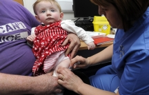 Ten-month old Lauren Durbin receives an injection for measles, mumps and rubella. Typically children do not receive the MMR vaccine until they are 12 months old.