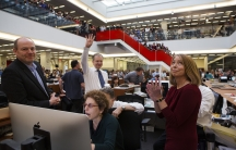Publisher Arthur Sulzberger Jr. holds up four fingers to indicate the four Pulitzer Prizes won by the New York Times in 2013 as Executive Editor Jill Abramson looks on.