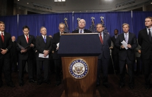 Eight men behind podium with microphones