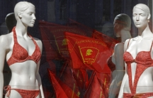 Communist flags are reflected in a lingerie shop window during a traditional Labor Day march in St. Petersburg in 2013.
