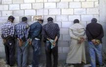 A handout photograph distributed by Syria's national news agency SANA shows detained men, blindfolded and handcuffed.