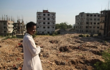 Rafiqul Islam is president of a labor federation based next to the site of the Rana Plaza collapse. In the foreground is a field filled with rubble from the building, and beyond that is the site of the collapse.
