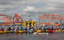 """""""Kayaktivists"""" demonstrate in Seattle's Elliot Bay against the arrival last month of the Shell's massive Polar Pioneer oil rig, rising behind them above the city's waterfront. Shell is using Seattle as a staging area for its new offshore drilling operatio"""