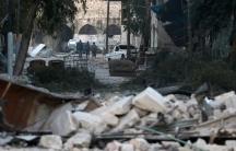 People walk near rubble of damaged buildings, in the rebel-held besieged area of Aleppo.