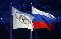 The Olympic and Russian flags are raised during the opening ceremony of the 2014 Sochi Winter Olympics.