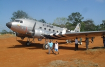 Pilots stand in the shade of the wing of a DC-3 in the hamlet of Miraflores in the Colombian jungle.
