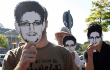 """Protesters hold masks depicting former US National Security Agency contractor Edward Snowden during a demonstration in Berlin on May 22, 2014. The sentence on the shirt reads, """"What has happened to revolution?"""""""