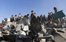 People search for survivors under the rubble of houses destroyed by an air strike near the Sanaa airport on March 26, 2015.