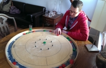 "Scott Philipps and his roommate own three Crokinole boards. Each board is over two feet in diameter and takes up a tabletop. The one pictured here is a ""regulation"" board used for tournament play."
