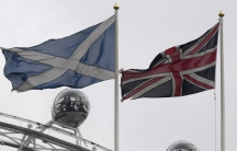 The British Union Flag, right, and a Scottish Saltire flag fly above the Scottish Office in Whitehall, with the London Eye wheel seen behind, in London.