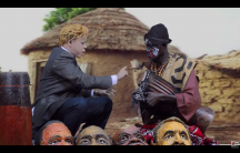 Kouthia, left, in character as Donald Trump visiting a Senegalese shaman.