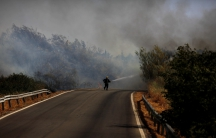 A firefighter works to put out a forest fire during a June heatwave in Southern Spain. Fires have plagued much of southern Europe this summer as the region has been hit by intense heat and drought.