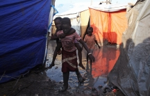 A South Sudanese girl displaced by the conflict carries a younger boy on her back as they walk through mud in a flooded camp for internally displaced people at the UNMISS base in Malakal, Upper Nile State May 30, 2014. There are about 18,000 people shelte