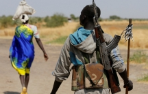 An armed man walks on a path near the village of Nialdhiu, South Sudan