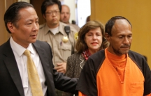 San Francisco Public Defender Jeff Adachi wearing a suit and tie leads Jose Ines Garcia Zarate, wearing prison orange, into court.