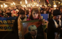 Activists of the Svoboda (Freedom) Ukrainian nationalist party hold torches as they take part in a rally to mark the 105th year since the birth of Stepan Bandera, one of the founders of the Organization of Ukrainian Nationalists (OUN), in Kiev. The portra