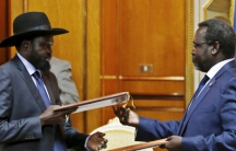South Sudan's rebel leader Riek Machar, at right, and South Sudan's President Salva Kiir exchange signed peace agreement documents in Addis Ababa in May 2014.