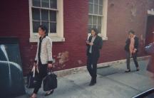 Three women walking on the sidewalk.