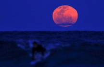 A surfer catches a wave as a super moon rises in the sky in Sydney, Australia. The astronomical event occurs when the moon is closest to the Earth in its orbit, making it appear much larger and brighter than usual.