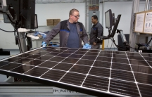 Production operator John White checks a panel at the SolarWorld solar panel factory in Hillsboro, Oregon.