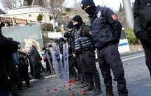 Flowers are placed next to Turkish police officers as they stand guard near the Reina nightclub, which was attacked by a gunman, in Istanbul, January 1.