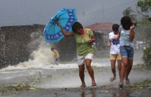 Residents walk along the coastal village while strong winds from Typhoon Haiyan battered Bayog town in Los Banos, Laguna, south of Manila November 8, 2013.