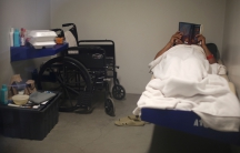 Man lies in bed in small room with wheelchair next to him