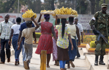Women carry baskets of banana as they walk past a military personnel patrolling in Uganda's capital Kampala, Feb. 19, 2016.