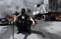 A protester sits in front of burning barricades during clashes with pro-government forces at Independence Square in Kiev, Ukraine on Aug. 7, 2014.