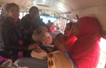 A group of women on a bus, with drums, singing