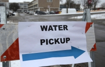 "A ""Water Pickup"" sign points to a bottled water distribution center in Flint, Michigan in January. In an effort to save money, state officials running Flint's affairs implemented changes to the city's water system that resulted in widespread lead contamin"