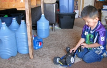 LaTanya Dickson's family has to travel 20 miles to get clean water, which they store in jugs under the kitchen table of their hogan on the Navajo Nation in northern Arizona.