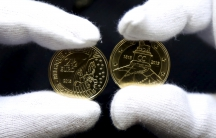 A worker displays newly minted commemorative 2.5 euro coins to mark the bicentennial of the battle of Waterloo.