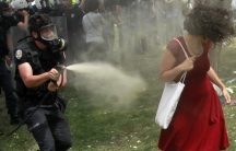 "A now-iconic picture of a Turkish riot policeman using tear gas against ""the woman in red,"" at an anti-government demonstration in Taksim Square, in the heart of Istanbul."